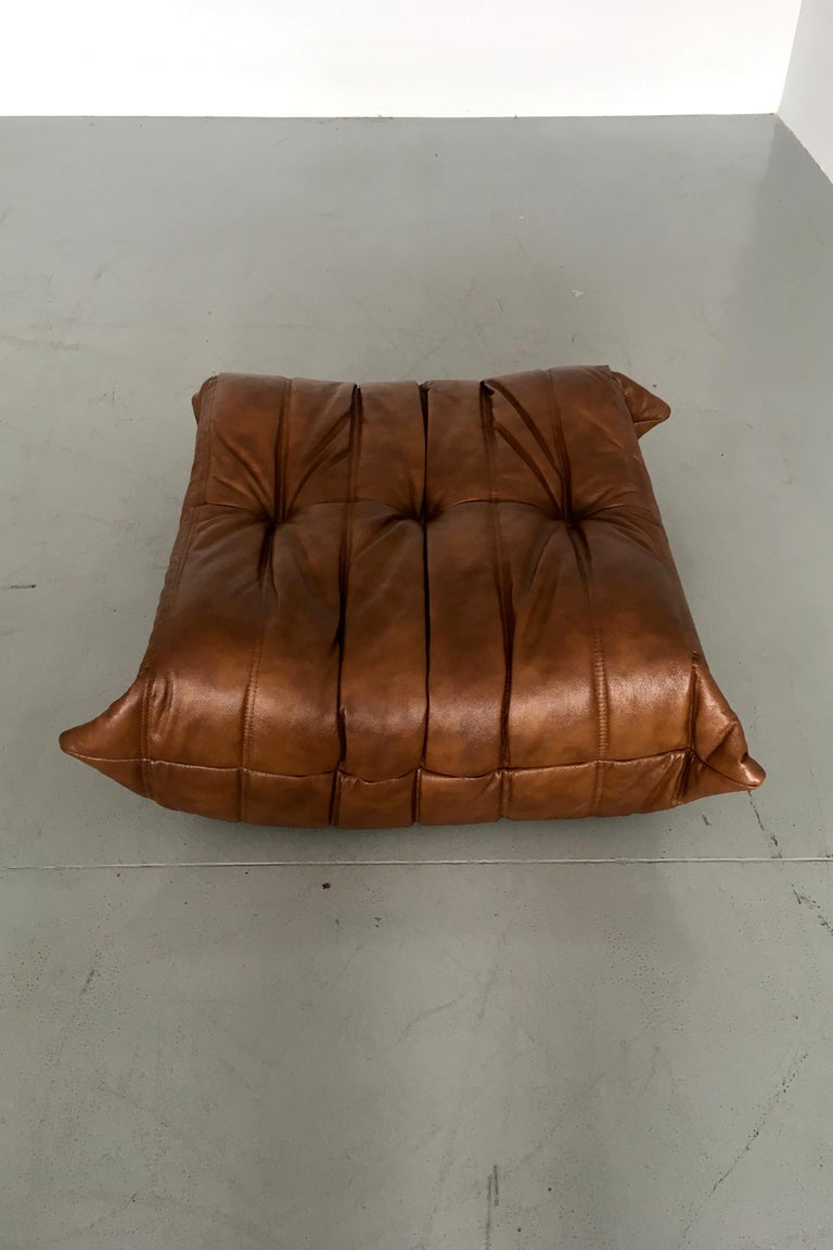 This Togo ottoman was designed by Michel Ducaroy in the 1970s and was manufactured by Ligne Roset in France. It has been reupholstered in new whiskey leather (87 x 80 x 38 cm). It has the original Ligne Roset logo and genuine Ligne Roset bottom.