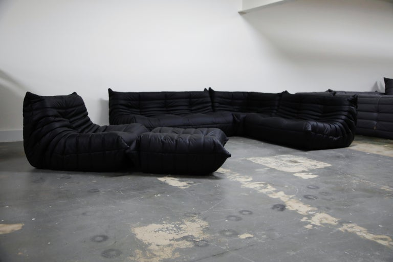 This incredible five (5) piece Togo sectional living room set, was designed by Michel Ducaroy in 1973 for Ligne Roset, France. This set was completely restored with new high grade Bovine leather upholstery in a soft black color, and bottom decking