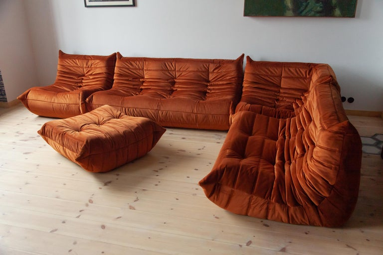 This Togo living room set was designed by Michel Ducaroy in 1973 and was manufactured by Ligne Roset in France. It has been reupholstered in new, great quality amber velvet and is made up of the following pieces: One three-seat couch (70 x 174 x 102