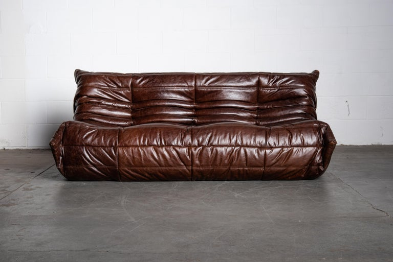 This incredible dark brown leather 'Togo' three-seat sofa was designed by Michel Ducaroy in 1973 for Ligne Roset, France. Signed with Ligne Roset underside decking fabric and label. Originally designed in the 1970s, this deep chocolate brown leather