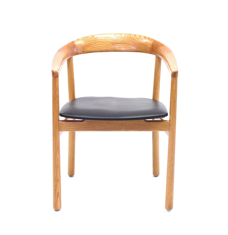 The 'Tokyo' armchair was originally designed by Carl-Axel Acking for the Swedish Embassy in Tokyo in 1959. This piece was manufactured in Sweden by Nordiska Kompaniet and is made from elm with new black vinyl upholstery. Close to mint condition.