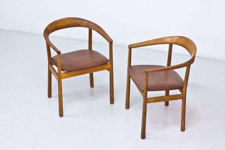 "Pair of ""Tokyo"" chairs designed by architect Carl-Axel Acking. Originally made for the Swedish Embassy in Tokyo, 1959. Manufactured by Nordiska Kompaniet (NK) in Sweden. Solid oak frame, newly reupholstered with patinated brown leather."