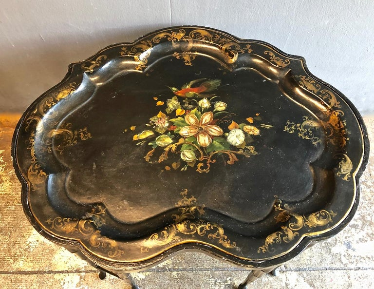 This is a good example of a mid-19th century English tole tray that has been fitted with a Regency style faux bamboo stand that most probably dates to the late 19th century. The scolloped edge tray is decorated with a central floral still life and