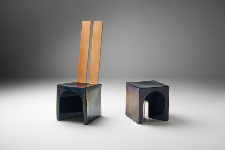 This elemental chair and table are a beautiful example of the collaboration between Dutch designer Tom Bruinsma and Mobach ceramics. These fully glazed ceramic pieces appear in a variety of colors depending on the angle and light. The wooden backs