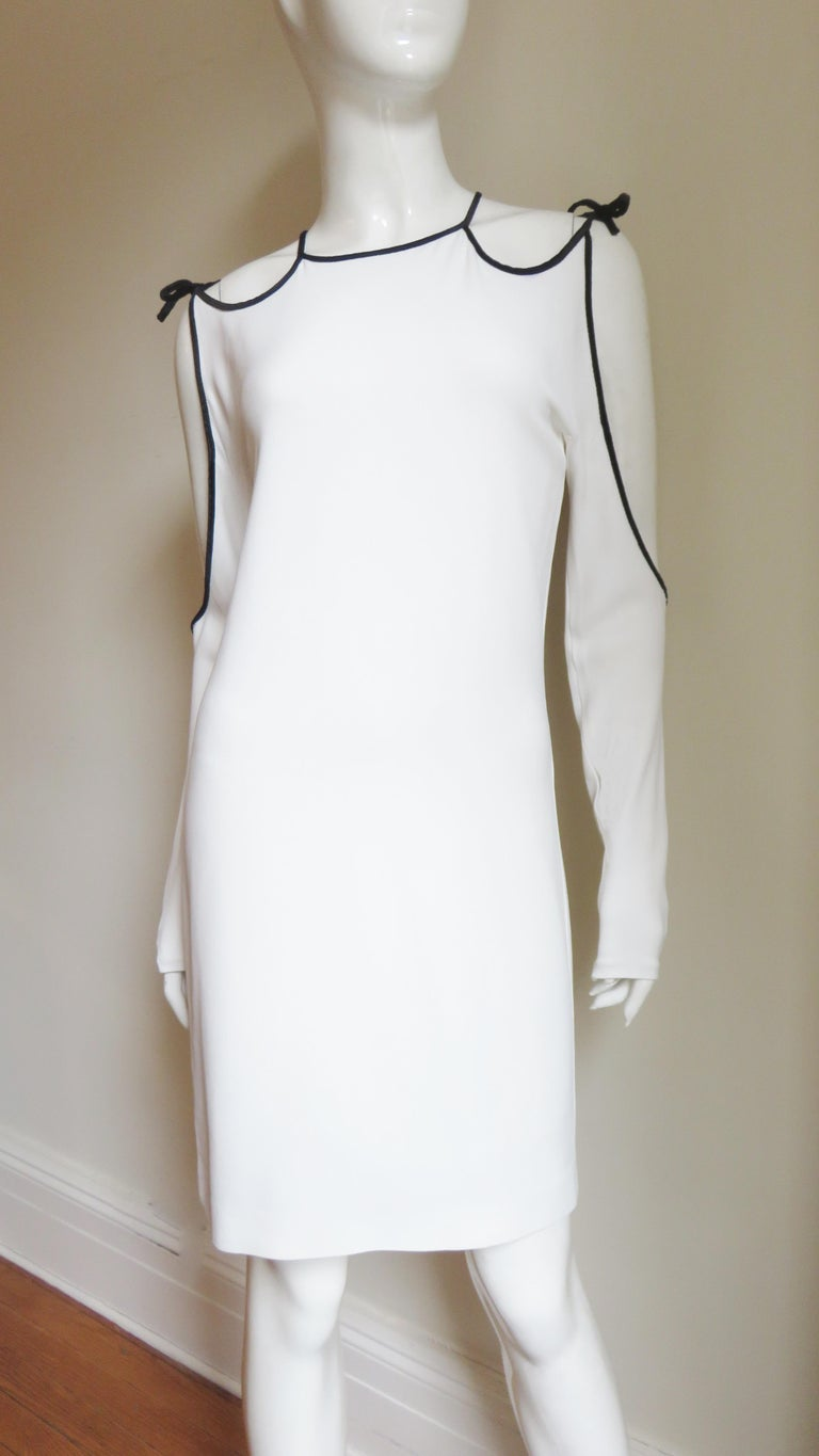 This is a fabulous white jersey dress from Tom Ford.  It has cut out shoulders, sleeves and back all framed in black velvet piping.  The dress is semi fitted then falls straight to the hem.  It is unlined, has ties at the shoulders, a hook closing