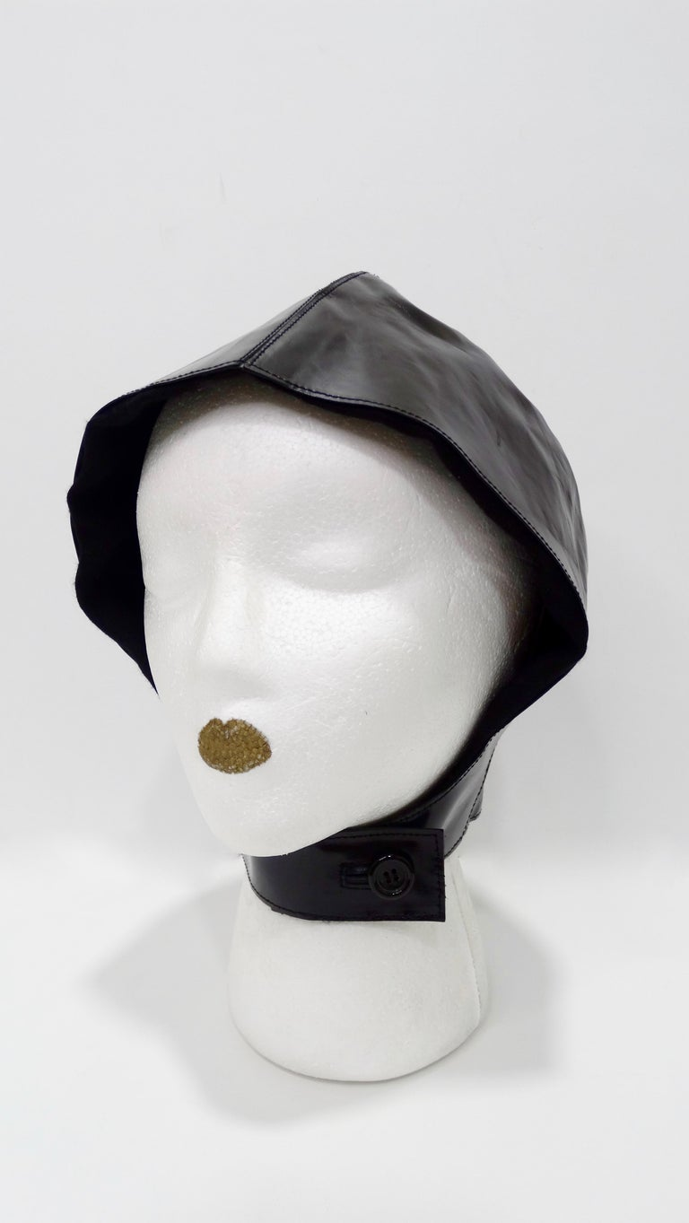 Straight from the Tom Ford archives! Circa 2003 from YSL's S/S collection, this flight cap is crafted from a shiny smooth black patient leather and is lined with cashmere and silk. Features a neckband that can be securely buttoned. Unique and a true