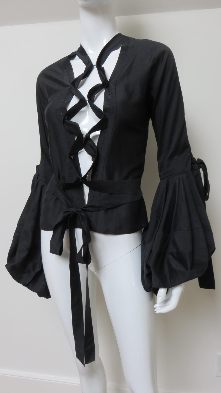 A fabulous iconic shirt blouse from Tom Ford for Yves St Laurent in a black fine silk cotton blend.  It is open in the front lacing up with bands of the fabric which attach to the blouse and together with black YSL inscribed mother of pearl buttons.