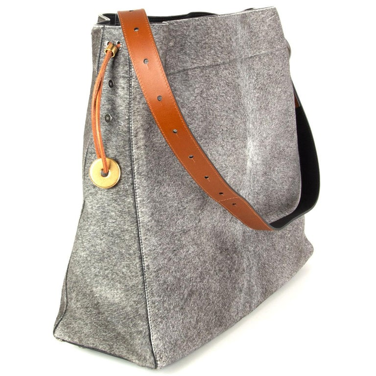 Tom Ford large hobo bag in grey calf hair with black and camel calfskin adjustable shoulder strap with gunmetal fisherman hook detail. Opens with a brown drawstring and is lined in black microfibre with one leather zip pocket and one open pocket.