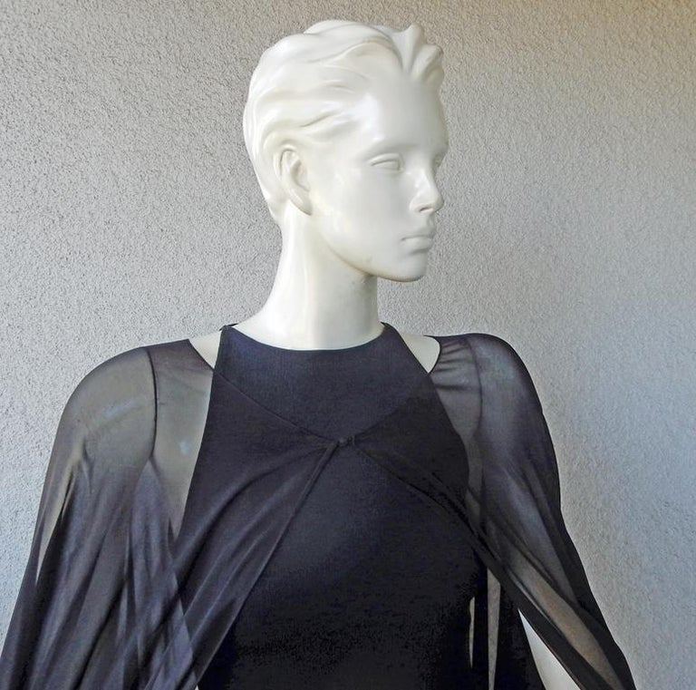 A signature style by Tom Ford in this version of a body hugging gown with high back kick pleat. A sheer black silk chiffon cape completes the look. Dramatic, elegant and sophisticated look. Very substantial. Clearly a design where less is