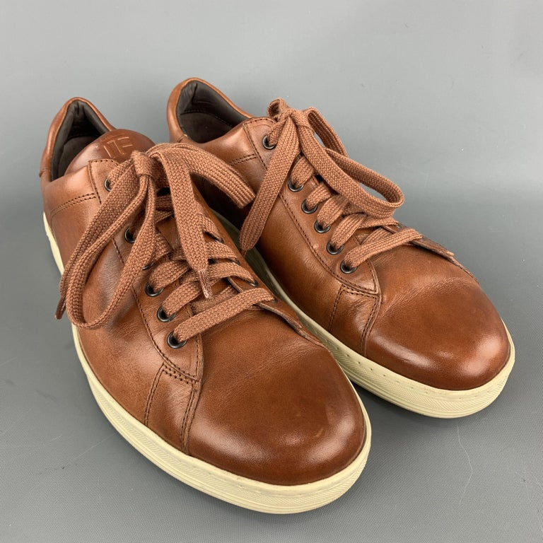 TOM FORD sneakers comes in a tan leather featuring a lace up style and a rubber sole. Made in Italy.  Excellent Pre-Owned Condition. Marked: 11  Outsole: 4 in. x 12 in.