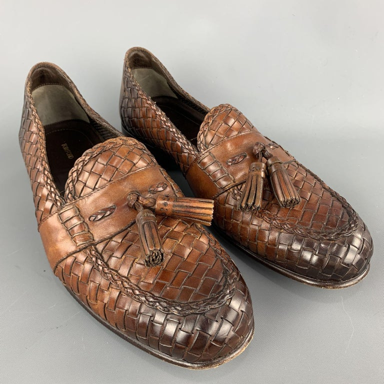 TOM FORD loafers comes in tan woven leather featuring a slip on style, front tassel details, and a wooden heel. Made in Italy.  Excellent Pre-Owned Condition. Marked: 11 T  Outsole: 4 in. x 12 in.