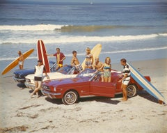 Friends with surfboards in Ford Mustangs