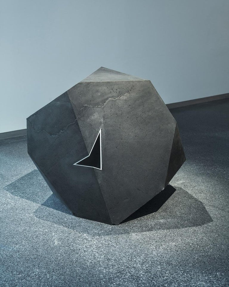 Coal, aluminium, Jesmonite. 100 cm × 100 cm × 100 cm. The artist created the Carbon Voids series by combining various geometric 'positive' (creating solids) and 'negative' (creating voids) shapes. In Carbon Void Blue, a resin triangle is nestled in