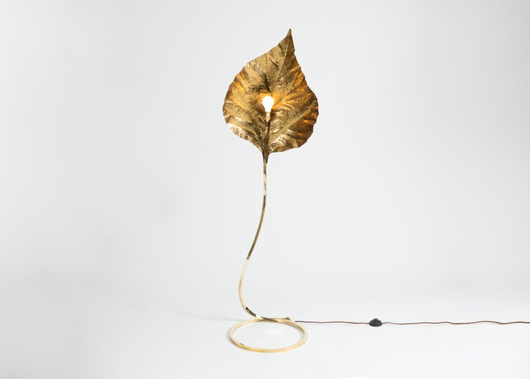 This extraordinary Italian floor lamp, a work of marvelous simplicity and elegance, is composed of brass, possesses a sinuous, elegant base, and features a show-stopping shade modeled perfectly after a broad, slightly folding leaf.