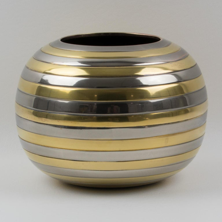 Interesting 1970s modernist vase, reminiscent of Tommaso Barbi's work. Space Age rounded shape with stripes in chrome and brass metal. No visible maker's mark. Measurements: 5.94 in. high (15 cm) x 8.07 in. diameter (20 cm).