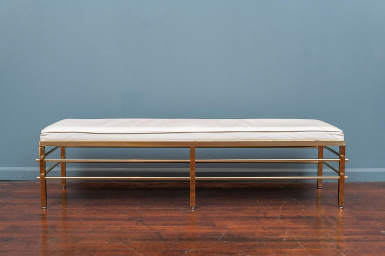 Tommi Parzinger design bench for Parzinger Originals, N.Y. Upholstered in what appears to be the original white leather on a brass tubular studded frame. A rare design made with high quality construction and attention to detail,