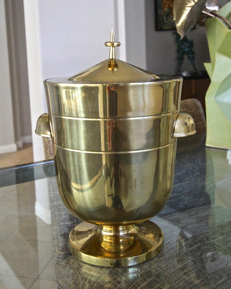 A fine lacquered brass lidded ice bucket or champagne cooler designed by Tommi Parzinger, including ice tongs. The ice bucket is in original almost new untouched condition. Stamped