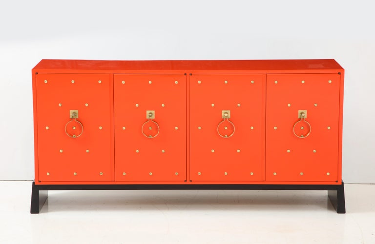 Tommi Parzinger credenza featuring 4 doors which conceal 2 storage compartments, 1 having a felt lined divided drawer, the other 2 adjustable shelves. Sideboard has been mint restored; color is based on the original coral orange color. Sides and