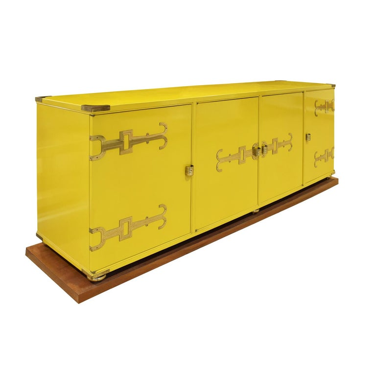 Exceptional credenza model #140 in yellow lacquer with iconic etched brass hardware, corner accents and sculptural ball feet which sit on a plinth base by Tommi Parzinger for Parzinger Originals, American 1950s. Since the lacquer is original and has