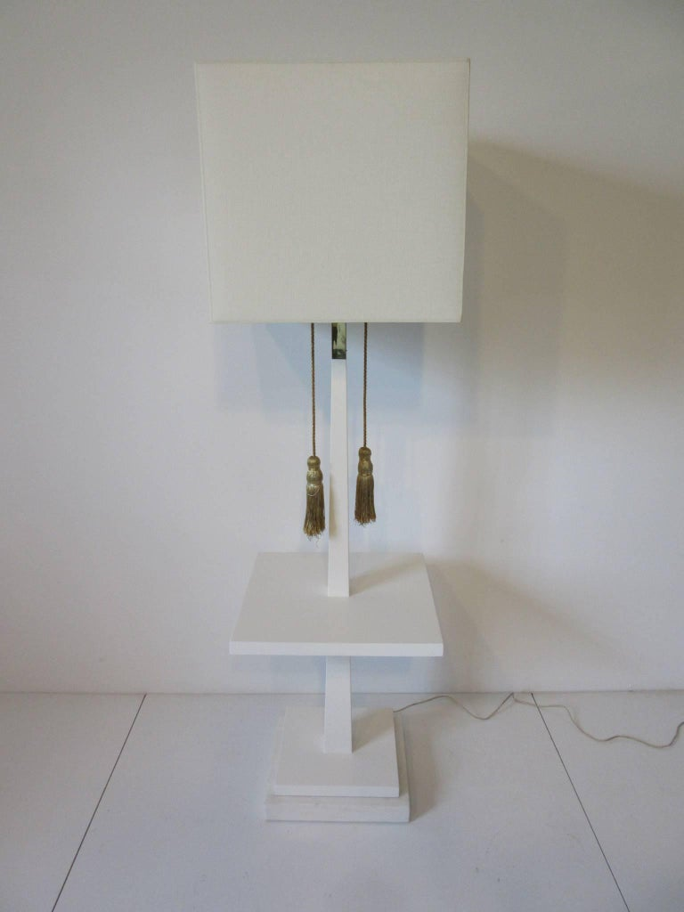 A satin white Regency styled wood floor lamp table with thick Carrara marble base and gold braided tassel lamp pulls, brass accent piece to the upper shaft. Retains the impressed mark to the base