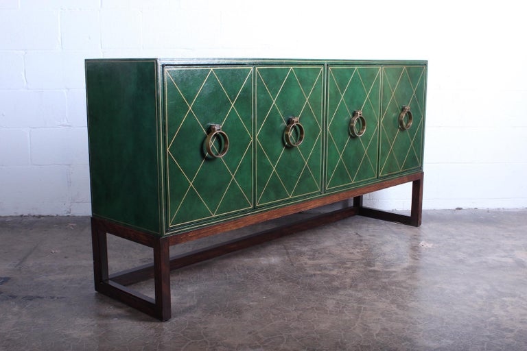 A leather clad cabinet with bronze hardware and mahogany base. Designed by Tommi Parzinger for Parzinger originals.