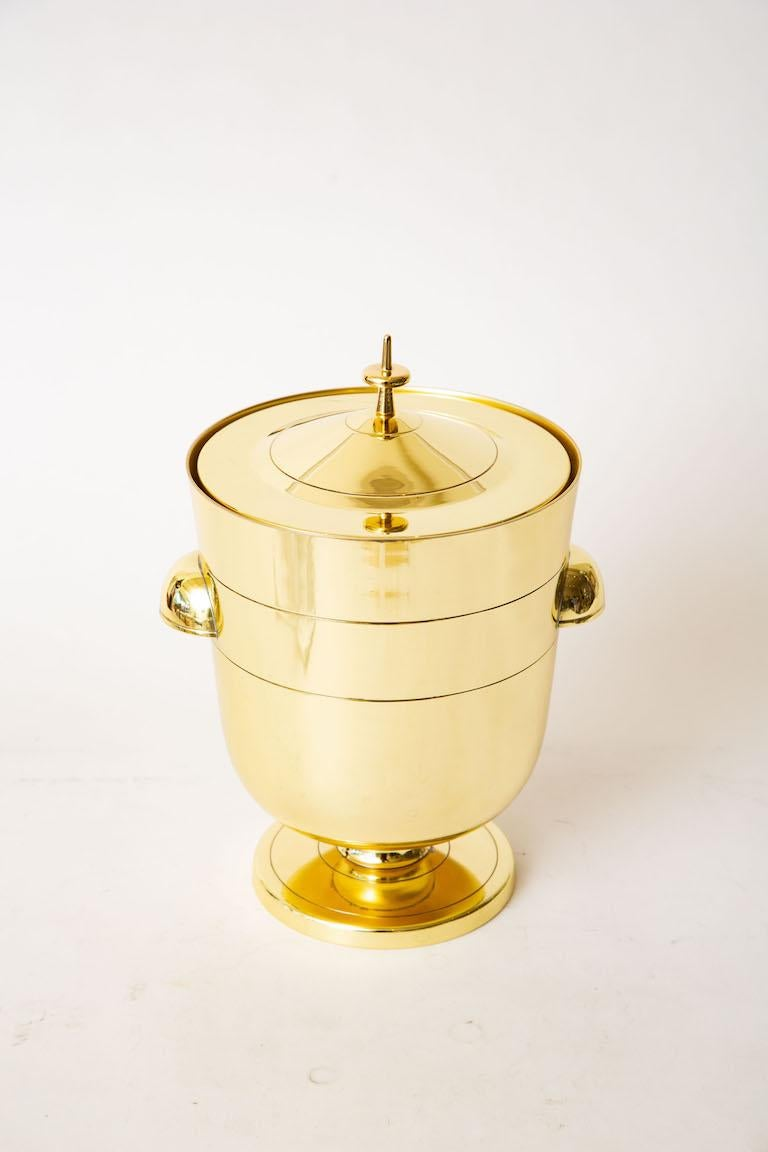 This iconic Mid-Century Modern lidded Tommi Parzinger brass ice bucket or champagne bucket is from the 50's. It has been newly polished and lacquered to prevent tarnishing. It retains the original mercury glass insert. This is a timeless and forever