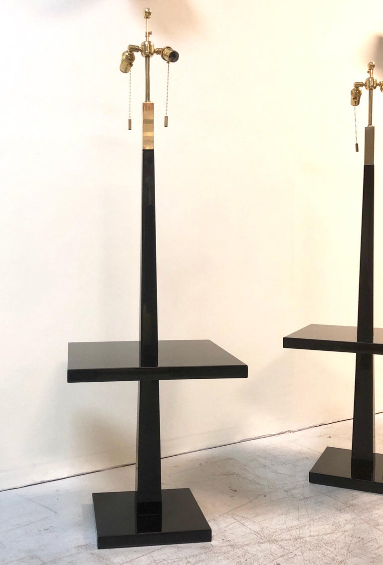 A pair of Parzinger lamps, being offered individually. They are wood with a new gloss piano finish. Brass accents. Re-wired and the obsolete glass torchiere top has been updated with a double cluster with an adjustable height tip.