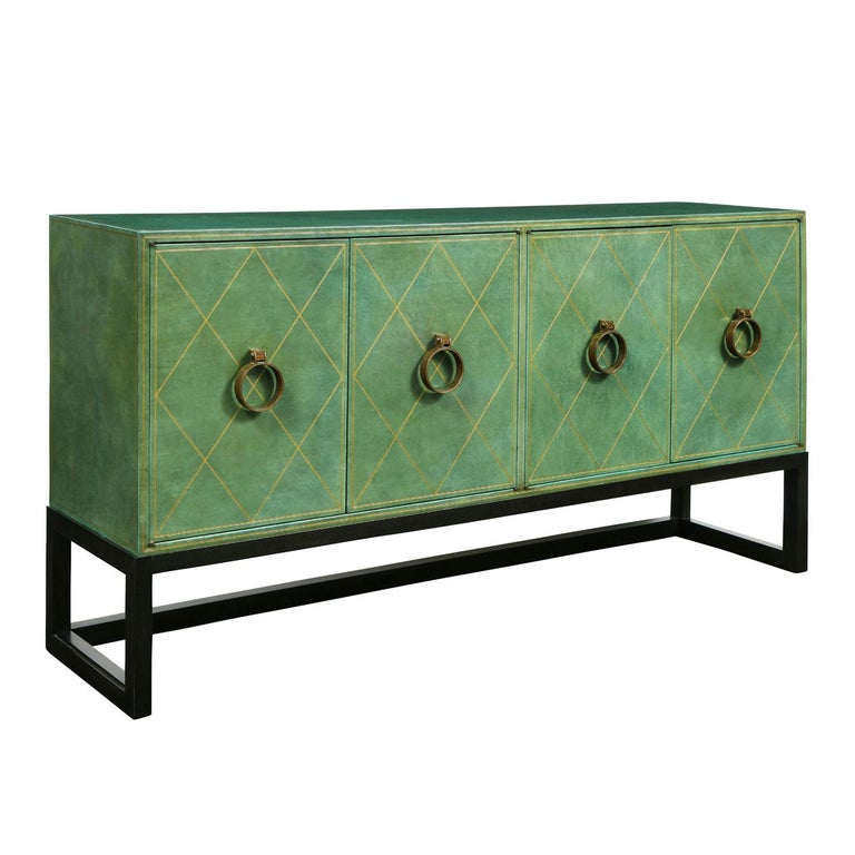 Beautifully crafted 4 door commode model TP-18 covered in hand-tooled emerald green leather with solid bronze handles on a dark mahogany base by Tommi Parzinger for Charak Modern American 1940's. The interior is lacquered pink. This is a rare and