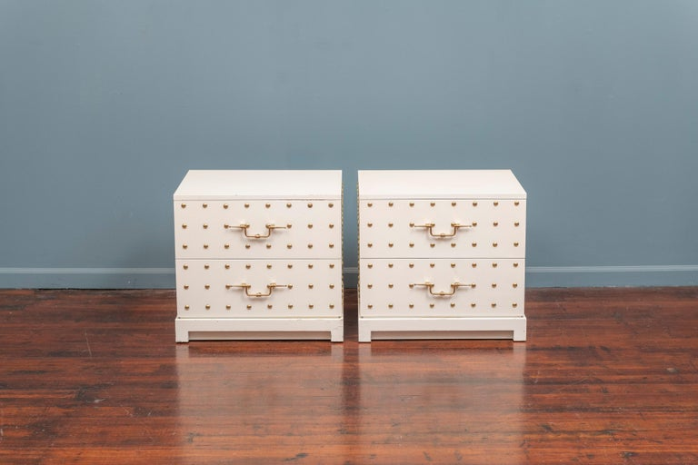 Tommi Parzinger pair of two-drawer white lacquered dressers inset with brass studs and original solid brass decorative handles. 