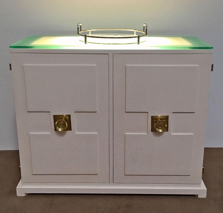 Illuminated two door bar cabinet designed by Tommi Parzinger. Features a frosted glass top that lights from underneath, two drawers, and adjustable shelves for storage. Handles and hinges are brass. This is a beautiful example of Parzinger's design.