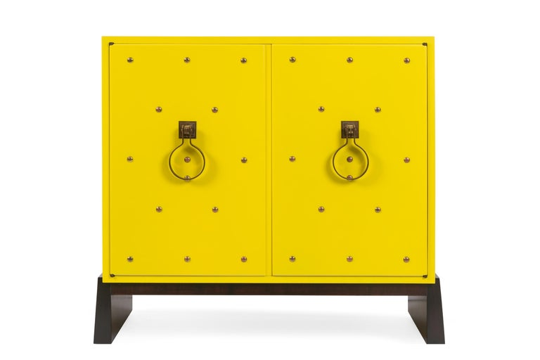 One of the most iconic pieces Parzinger designed was the studded cabinet with brass knocker pulls. This example has been beautifully restored to its original yellow lacquer finish.