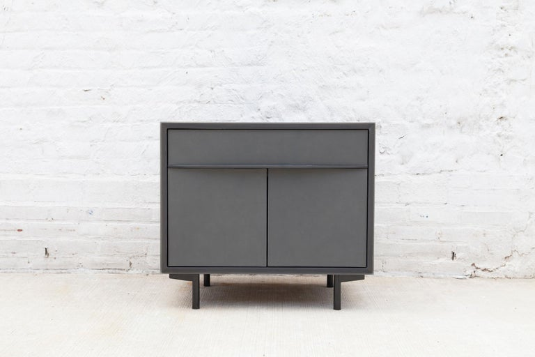 The sleek Tompkins end table has a blackened aluminum encased in epoxy resin exterior. The doors and drawer face are wrapped in leather with blackened steel pulls. The walnut dovetail drawer is lined with black leather and the interior cabinet has