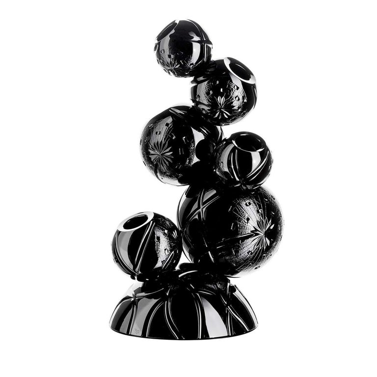 Striking and unique, the design of this vase and its black color create a piece of strong visual impact that will make a statement in a modern interior. The semi-spherical base supports a series of spheres of different sizes balanced one on the