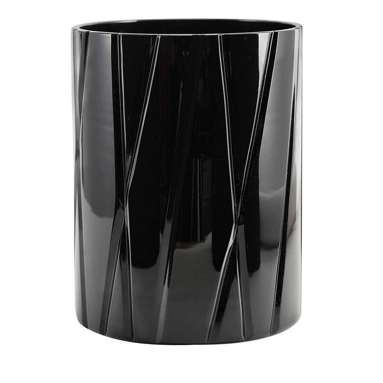 An exercise in elegant minimalism, this black crystal vase is part of the Skyline collection, recreating in a stylized fashion the vertical tension of the modern city's skyscrapers. Either alone, to complement a contemporary interior, or combined