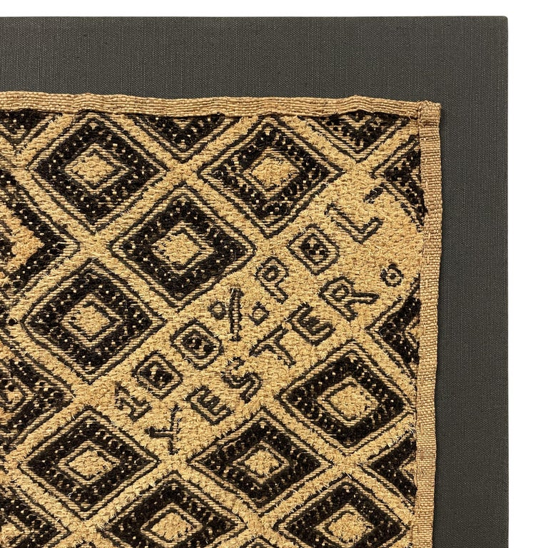 A provocative late 20th century Kuba cloth panel with a bold zigzag and diamond pattern woven in black and natural cut pile raffia surrounding a tongue-in-cheek inscription reading,