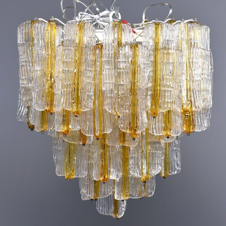 Venini chandelier designed by Toni Zuccheri for Venini features tiers of ribbed clear glass pendants with amber centers. Six regular sized sockets. Chandelier has been rewired for US electrical standards, circa late 1960s-early 1970s.