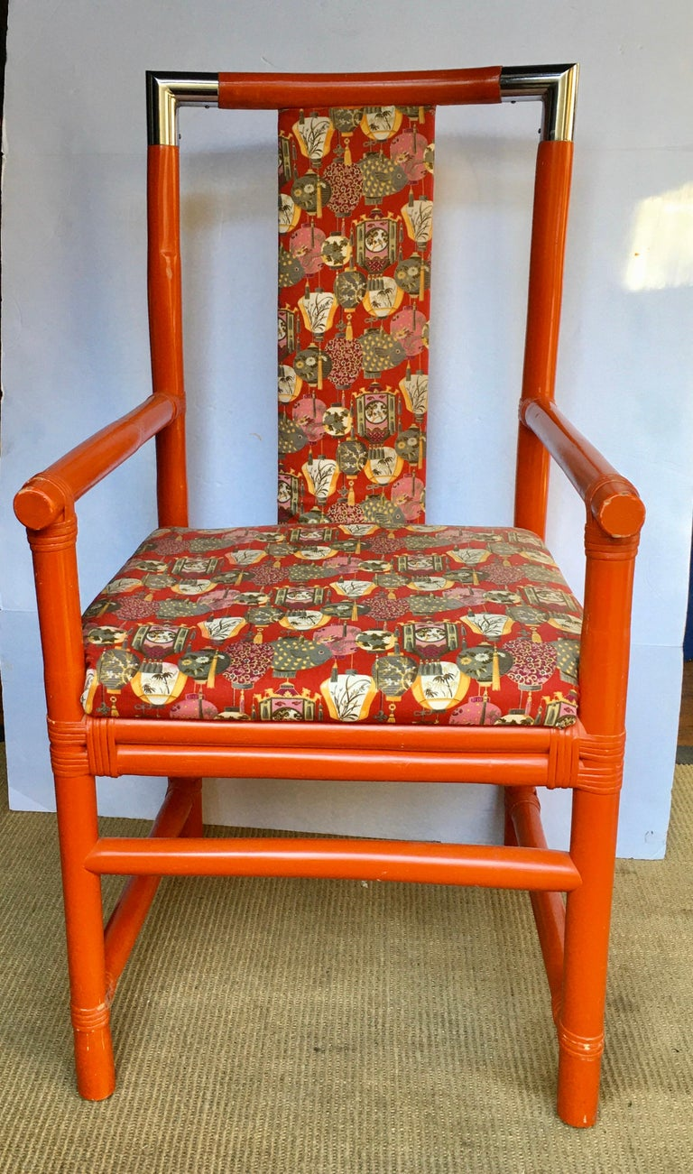 Mid-Century Modern vibrant orange painted wood bamboo accent chair with metal chrome accents. Chair frame is constructed of thick sturdy bamboo reeds connected by polished chrome corner end caps. Upholstered in an Asian motif upholstery. A perfect