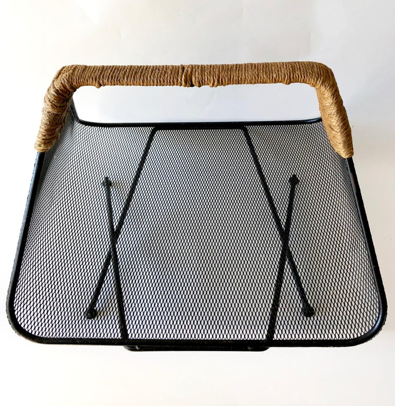 Iron mesh with rush wrapped handle by Tony Paul for Woodlin-Hall magazine rack or log holder, circa 1950's. Measures 15