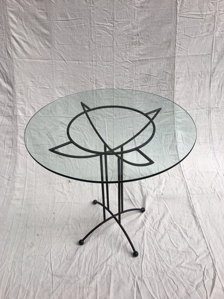Tony Paulstyle glass and iron table. Great size for small spaces, use inside or out! Rubber ball feet and Geometric Design gives this table an extra kick!