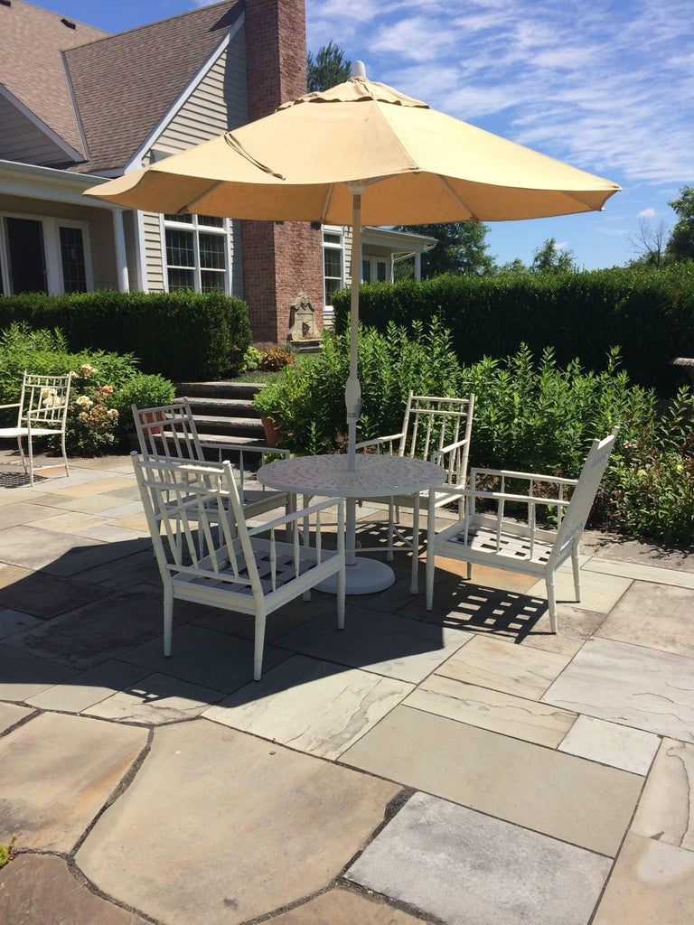 Luxurious round bistro table and four arm chairs in white cast aluminium with big shade umbrella. Looks like it belongs in a five star resort.  Made by Summer Classics.  Sunbrella fabric. Chairs have plush custom cushions and measure 22 W, 22 D, 35