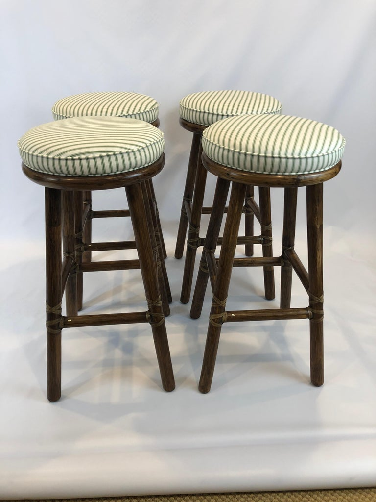 Beautifully made as only McGuire does it, a handsome set of 4 substantial tobacco colored bamboo bar stools having leather bindings and attached green and white striped seat cushions. Bottom is 15.75 square.