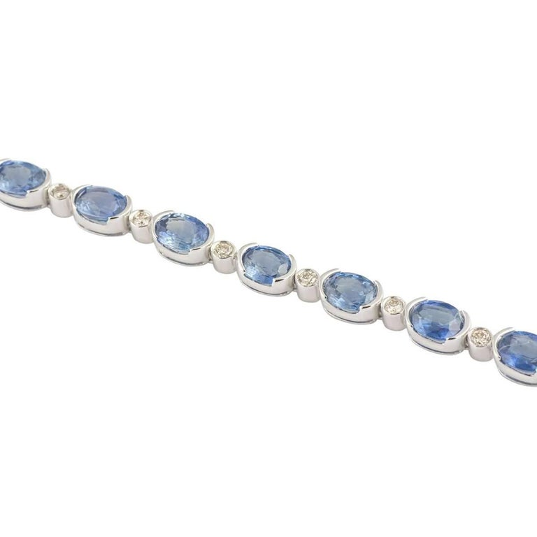 An 18k white gold blue topaz and diamond line bracelet. The bracelet is set with 22 oval cut blue topaz stones and 22 round brilliant cut diamonds. The topaz has a total carat weight of approximately 7.92ct and the diamonds total approximately