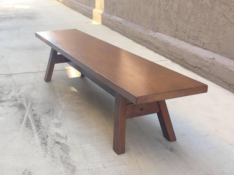 Walnut bench form with four splayed legs and trestle support.