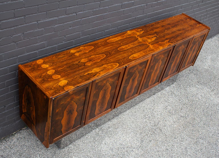 Spectacular vintage 1960s book-matched, double bleached Brazilian rosewood credenza with mirror-polished plinth base. This cabinet was custom ordered from Bruksbo of Norway by the owner of a Danish Modern design store in San Francisco for her own