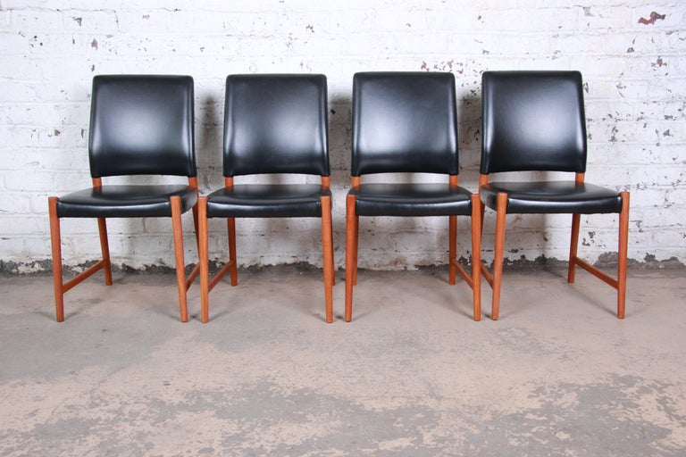 A gorgeous set of four midcentury Danish modern dining chairs designed by Torbjorn Afdal for Nesjestranda Møbelfabrik of Norway. The chairs feature solid teak frames and beautiful black leather upholstery. Stamped