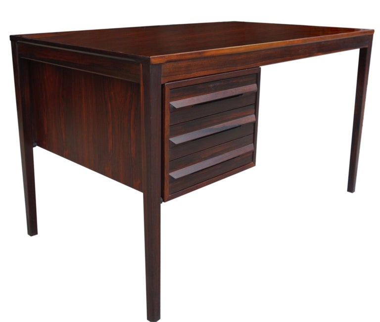 For your consideration is this classic Brazilian rosewood desk featuring three drawers on the left side. Finished on both sides showing beautifully and ready for use. A wonderful example of Danish midcentury design.   kneehole opening height is