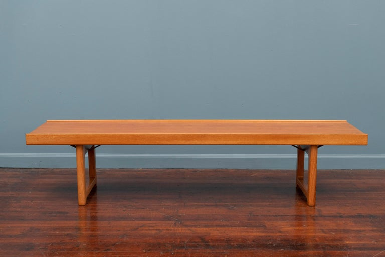 Bench or coffee table designed by Torbjørn Afdal for Bruksbo in Norway circa 1960s. A versatile and playful design featuring a beautiful and distinct teak wood grain over the rectangular, raised lip top and supported by sculpted geometric legs. Its