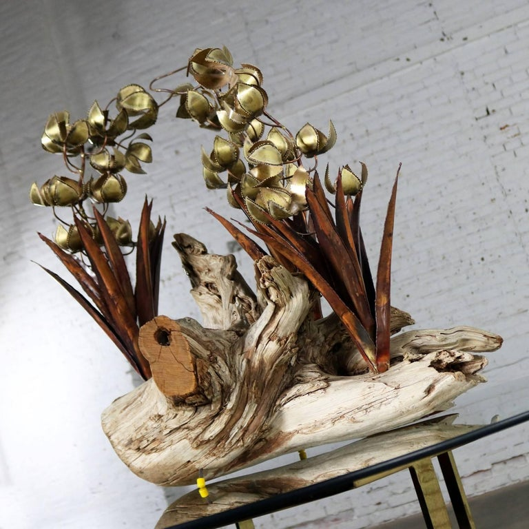 Incredible Brutalist torch cut copper and brass floral sculpture on driftwood. Unsigned but done in the style of Silas Seandel or C. Jere. It is in excellent vintage condition, circa 1970s.  This is the most stunning floral sculpture I believe I