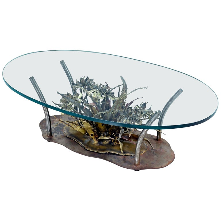 Brutalist Mid-Century Modern coffee table by Silas Seandel. The undulating oval shaped base features a large, organic floral sculpture made of patinated metal with copper, steel, gold and brass tones. The base is topped with a thick oval shape glass