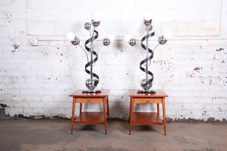 An exceptional pair of oversized Torino style Mid-Century Modern Space Age Sputnik table lamps. The lamps feature heavy chrome frames, each with four arms and a unique ebonized bentwood corkscrew design. They offer three-way lighting, and each lamp